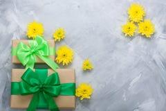 Geschenkboxblumenstrauß-Gelbchrysanthemen auf grauem konkretem backgrou Lizenzfreies Stockbild