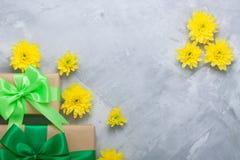 Geschenkboxblumenstrauß-Gelbchrysanthemen auf grauem konkretem backgrou Lizenzfreie Stockfotografie