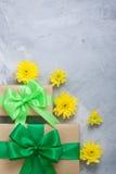 Geschenkboxblumenstrauß-Gelbchrysanthemen auf grauem konkretem backgrou Stockbild