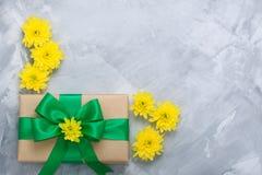 Geschenkboxblumenstrauß-Gelbchrysanthemen auf grauem konkretem backgrou Lizenzfreies Stockfoto
