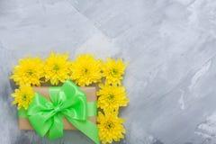 Geschenkboxblumenstrauß-Gelbchrysanthemen auf grauem konkretem backgrou Stockfotografie