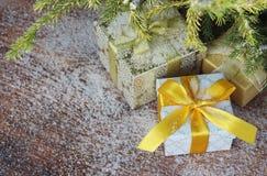 Geschenkboxen auf hölzernen Hintergrund- und Tannenbaumniederlassungen stockfoto
