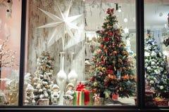 Geschenkboxen, Bonbons und Weihnachtsdekor im Shopfenster Lizenzfreies Stockbild
