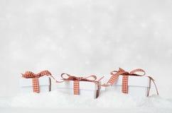 Geschenkboxen der weißen Weihnacht im Schnee mit Bokeh-Hintergrund Lizenzfreie Stockfotos