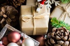Geschenkboxen des neuen Jahres und des Weihnachten eingewickelt im Kraftpapier, Kiefernkegel, Flitter, Weihnachtsmann-Zahl, Tanne Lizenzfreies Stockfoto
