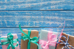 Geschenkboxen im Papier auf einem blauen Holztisch Lizenzfreie Stockbilder