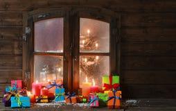 Geschenkboxen und Kerzen am Fenster auf Weihnachten Lizenzfreies Stockfoto