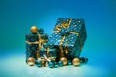 Geschenkboxen und Weihnachtsbälle, lokalisiert auf blauem Hintergrund Lizenzfreies Stockbild