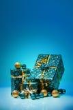 Geschenkboxen und Weihnachtsbälle, lokalisiert auf blauem Hintergrund Lizenzfreie Stockbilder