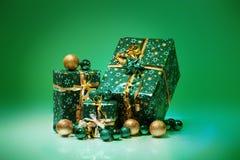 Geschenkboxen und Weihnachtsbälle, lokalisiert auf grünem Hintergrund Lizenzfreies Stockfoto