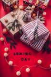 Geschenkboxen verziert mit Tannenzweigen auf rotem Hintergrund 26. Dezember-Hintergrund Stockfotos