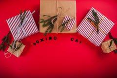 Geschenkboxen verziert mit Tannenzweigen auf rotem Hintergrund 26. Dezember-Hintergrund Lizenzfreie Stockfotografie