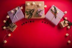 Geschenkboxen verziert mit Tannenzweigen auf rotem Hintergrund 26. Dezember-Hintergrund Lizenzfreie Stockfotos