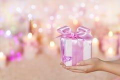 Geschenkboxen, welche an die Hände, rosa Geschenk gebend, Mädchen-Frau halten Stockfotos