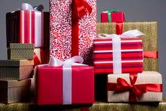 Geschenke auf einem roten Hintergrund für einen Feiertag, Weihnachten, Jahrestag Stockbilder
