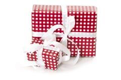 Geschenke eingewickelt im karierten roten Papier mit einem weißen Band Stockfotos