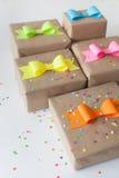 Geschenke eingewickelt im Kraftpapier Farbige helle Papierbögen Stockfotografie