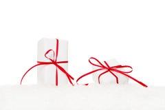 Geschenke eingewickelt im Weißbuch und mit rotem Band gebunden Lizenzfreie Stockfotos
