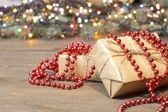 Geschenke eingewickelt in Kraftpapier, helle Girlande Lizenzfreie Stockfotos