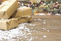 Geschenke eingewickelt in Kraftpapier, helle Girlande Lizenzfreies Stockbild