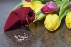 Geschenke für geliebte Ein Blumenstrauß von gelben und rosa Tulpen wird auf eine dunkle Oberfläche zerstreut Ist in der Nähe eine Lizenzfreie Stockfotografie