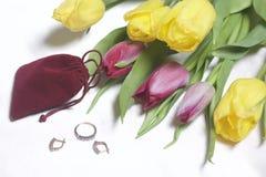 Geschenke für geliebte Ein Blumenstrauß von gelben und rosa Tulpen wird auf eine helle Oberfläche zerstreut Ist in der Nähe eine  Stockbild
