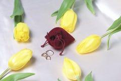 Geschenke für geliebte Ein Blumenstrauß von gelben und rosa Tulpen wird auf eine helle Oberfläche zerstreut Ist in der Nähe eine  Lizenzfreies Stockbild
