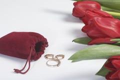 Geschenke für geliebte Ein Blumenstrauß von roten Tulpen wird auf eine weiße Oberfläche zerstreut Ist in der Nähe eine rote Samtt Lizenzfreie Stockfotografie