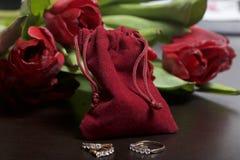 Geschenke für geliebte Ein Blumenstrauß von roten Tulpen wird auf eine weiße Oberfläche zerstreut Ist in der Nähe eine rote Samtt Lizenzfreies Stockfoto