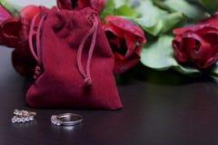 Geschenke für geliebte Ein Blumenstrauß von roten Tulpen wird auf eine weiße Oberfläche zerstreut Ist in der Nähe eine rote Samtt Stockfotografie