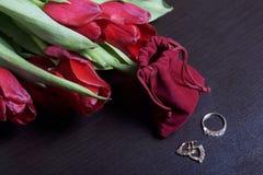 Geschenke für geliebte Ein Blumenstrauß von roten Tulpen wird auf eine weiße Oberfläche zerstreut Ist in der Nähe eine rote Samtt Lizenzfreie Stockbilder