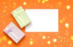 Geschenke und ein Blatt Papier für die Aufschrift auf einem orange Hintergrund mit Weihnachtslichtern stockfotos