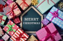 Geschenke und frohe Weihnachten des Textes in der Tafel Stockfotografie