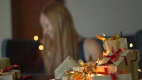 Geschenke und Gespräch eines der jungen Frau Satzes auf einem Mobiltelefon Geschenk eingewickelt im Kraftpapier mit einem Rot- un stock video