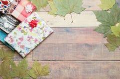 Geschenke und Herbstlaub auf Holztisch Stockbilder