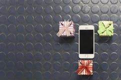 Geschenke und intelligentes Telefon auf dem Hintergrund Lizenzfreie Stockbilder