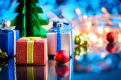 Geschenke und Spielwaren auf Glastisch- und bokeh Blaulichthintergrund Lizenzfreie Stockbilder