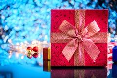 Geschenke und Spielwaren auf Glastisch- und bokeh Blaulichthintergrund Stockfotografie