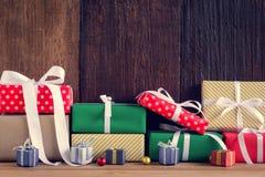 Geschenke und Spielwaren auf hölzernen Brettern mit Weihnachtsfeiertagen Lizenzfreie Stockfotos