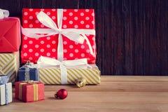 Geschenke und Spielwaren auf hölzernen Brettern mit Weihnachtsfeiertagen Stockfotografie