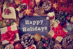 Geschenke und Weihnachtsverzierungen und der Text frohe Feiertage Stockfotos