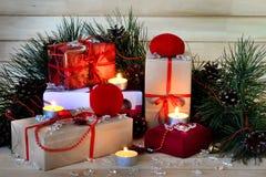 Geschenke und Zweige der Kiefer mit Kegeln, Kerzen auf hölzernem Hintergrund Lizenzfreie Stockfotos