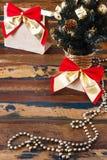 Geschenke verpacken mit rotem goldenem Bogen nahe kleinem Weihnachtsbaum Stockbild