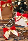 Geschenke verpacken mit rotem goldenem Bogen nahe kleinem Weihnachtsbaum Lizenzfreie Stockfotos
