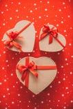 Geschenkherz mit rotem Band auf einer Draufsicht des roten Hintergrundes Stockbild
