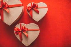 Geschenkherz mit rotem Band auf einer Draufsicht des roten Hintergrundes Stockfotografie