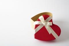 Geschenkherzkasten auf dem weißen Hintergrund Rotes Farbband Blumenstrauß von Rosen im Hintergrund Stockbild