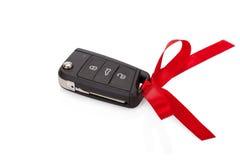 Geschenkidee: Autoschlüssel mit dem roten Band lokalisiert Lizenzfreie Stockfotos