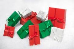 Geschenkkästen getrennt auf weißem Hintergrund im Schnee. Lizenzfreie Stockfotos