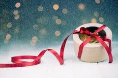 Geschenkkasten mit rotem Farbband Fallender Effekt des Schnees lizenzfreies stockbild